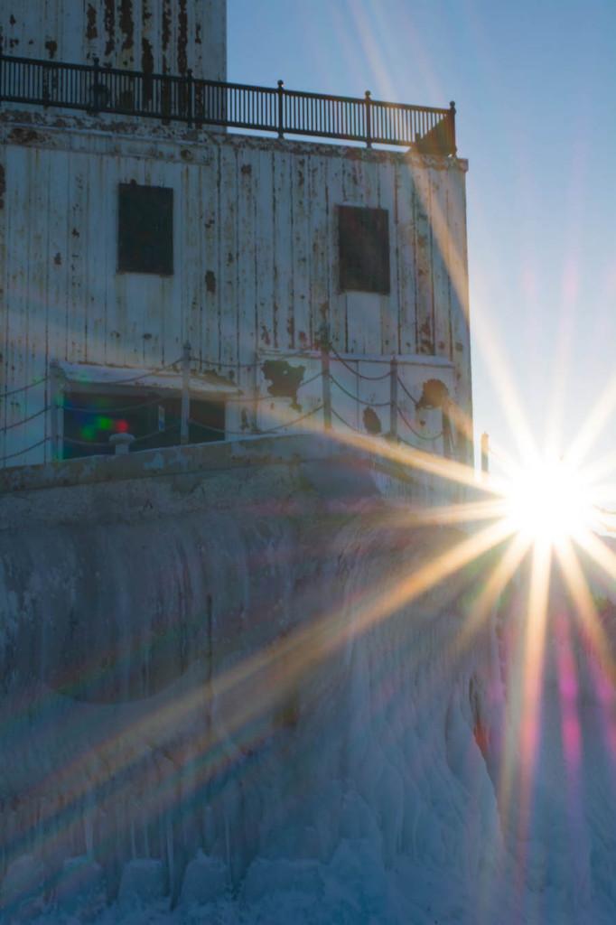 The sun setting behind the Crib lighthouse on Lake Michigan